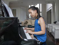 Girl playing the piano Royalty Free Stock Photo