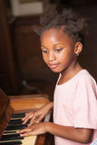 Girl playing piano Stock Photography