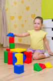 Girl playing with plasic cubes Stock Images