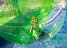 Girl playing in a plastic ball on water Royalty Free Stock Photos