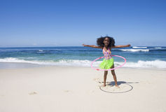 Girl (6-8) playing with plastic hoop near water's edge on sandy beach, arms out, front view, portrait Royalty Free Stock Image