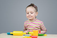 Girl playing with plastic tableware Royalty Free Stock Images