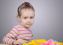 Girl playing with plastic tableware Royalty Free Stock Photography
