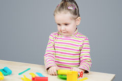 Girl playing with plastic tableware Stock Image