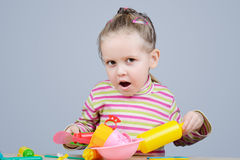 Girl playing with plastic tableware Stock Photography