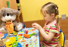 Girl playing with plasticine Stock Images