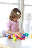 Girl playing with play dough. Little girl is learning to use colorful play dough in a well lit room near window Royalty Free Stock Images