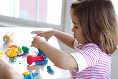 Girl playing with play dough. Little girl is learning to use colorful play dough in a well lit room near window Stock Image