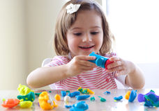Girl playing with play dough. Little girl is learning to use colorful play dough in a well lit room near window Stock Photos