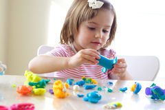 Girl playing with play dough. Little girl is learning to use colorful play dough in a well lit room near window Stock Photography