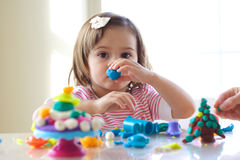 Girl playing with play dough. Little girl is learning to use colorful play dough in a well lit room near window Royalty Free Stock Image