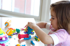 Girl playing with play dough. Little girl is learning to use colorful play dough in a well lit room near window Stock Photo