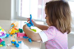 Girl playing with play dough. Little girl is learning to use colorful play dough in a well lit room near window Royalty Free Stock Photo