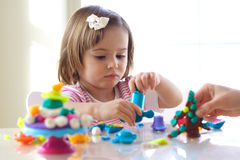 Girl playing with play dough. Little girl is learning to use colorful play dough in a well lit room near window Royalty Free Stock Photography