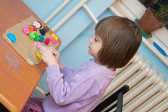 Girl playing with play dough - plasticine Royalty Free Stock Image
