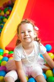 Girl playing on the playground, in the children`s maze with ball royalty free stock photos