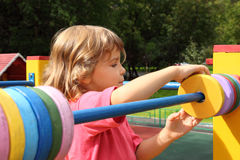 Girl playing at playground in summer sunny day Royalty Free Stock Images