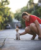 Girl playing with pomeranian puppy dog in home village Royalty Free Stock Image