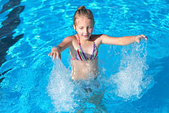 Girl playing in the pool. With blue clear water Royalty Free Stock Photography
