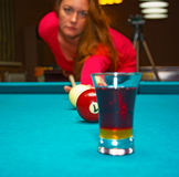 Girl playing pool, has the ball and is reflected in the glass stock photo