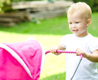 Girl playing with a pram for dolls royalty free stock photos