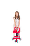 Girl playing with pram toy Royalty Free Stock Images