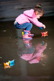 Girl playing in puddle. Little girl, wearing a pink jacket, playing with colorful paper ship, in the puddle Stock Image