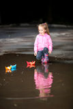 Girl playing in puddle. Little girl, wearing a pink jacket, playing with colorful paper ship, in the puddle Royalty Free Stock Photos