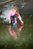 Girl playing in puddle. Little girl, wearing a pink jacket, playing with colorful paper ship, in the puddle Stock Photography