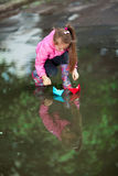 Girl playing in puddle. Little girl, wearing a pink jacket, playing with colorful paper ship, in the puddle Stock Images