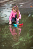 Girl playing in puddle. Little girl, wearing a pink jacket, playing with colorful paper ship, in the puddle Royalty Free Stock Image