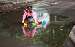 Girl playing in puddle. Little girl, wearing a pink jacket, playing with colorful paper ship, in the puddle Stock Photos