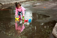 Girl playing in puddle. Little girl, wearing a pink jacket, playing with colorful paper ship, in the puddle Royalty Free Stock Images
