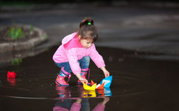 Girl playing in puddle Stock Photography