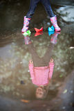 Girl playing in puddle. Little girl, wearing a pink jacket, playing with colorful paper ship in the puddle Royalty Free Stock Photo