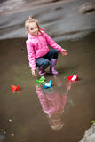 Girl playing in puddle. Little girl, wearing a pink jacket, playing with colorful paper ship, in the puddle Royalty Free Stock Photography