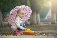 A girl playing in the puddle with the boat after rain stock image