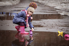 Girl playing in puddles Stock Photos