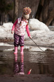 Girl playing in puddles Stock Image