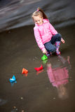 Girl playing in puddles. Little girl, wearing a pink jacket, playing with colorful paper ship, in the puddle Royalty Free Stock Photos