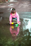 Girl playing in puddles. Little girl, wearing a pink jacket, playing with colorful paper ship, in the puddle Stock Photos
