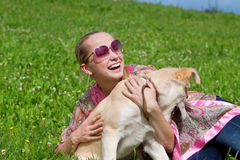 Girl playing with a puppy. Beautiful young girl playing with a puppy on the grass Stock Photo