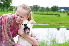 Girl playing with a puppy, summer day. Beautiful young girl playing with a puppy on the meadow Royalty Free Stock Image