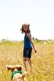 Girl playing with a puppy in tall grass royalty free stock images