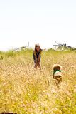 Girl playing with a puppy in tall grass Royalty Free Stock Photography