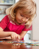 Girl, playing puzzles Stock Photography
