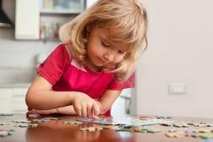 Girl, playing puzzles Stock Photos