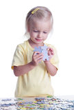 Girl playing puzzles Stock Images
