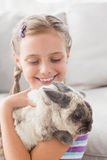 Girl playing with rabbit in living room Royalty Free Stock Photos