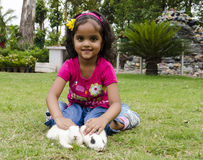Girl playing with Rabbits. Royalty Free Stock Image